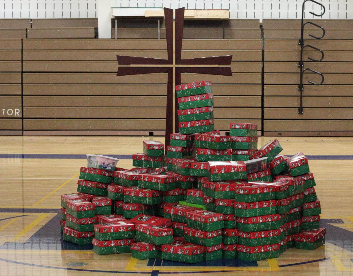 Operation Christmas Child boxes at the foot of a cross